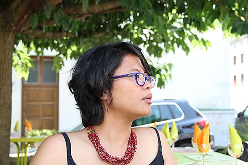 Portrait de Nathalie Muchamad à la terrasse d'un restaurant, sous un arbre.