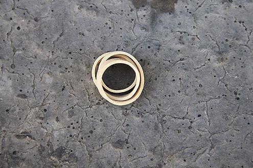 Photo d'un elastique enroulé sur lui même donnant un tuyau sur un sol de béton craquélé