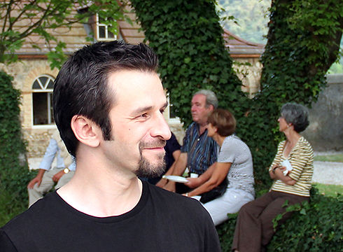 Portrait de Ludovic Paquelier dans un parc, des gens et une maison derrière lui.