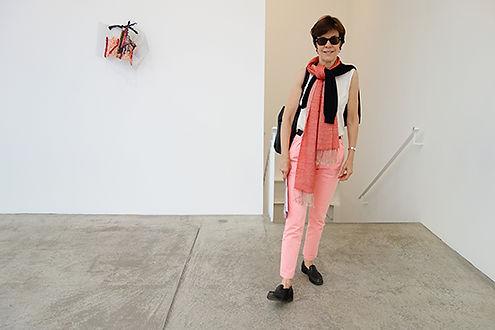 Portrait en pied de Florence Pierre avec une oeuvre de Richard Tuttle à la galerie Mariane Goodman