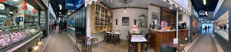 Photo panoramique du café Jocteur aux Halles Paul Bocuse de Lyon montrant l'avant et l'arrière d'une même travée