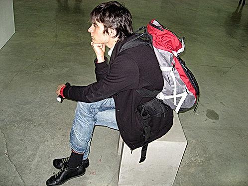 Portrait de Baptiste Croze assis sur un cube, méditant avec un énorme sac à dos.