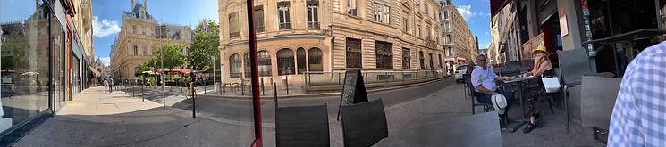 Photo panoramique de la rue de la Bourse avec la terrasse du bar le Hall de la Bourse avec deux personnes attablées.