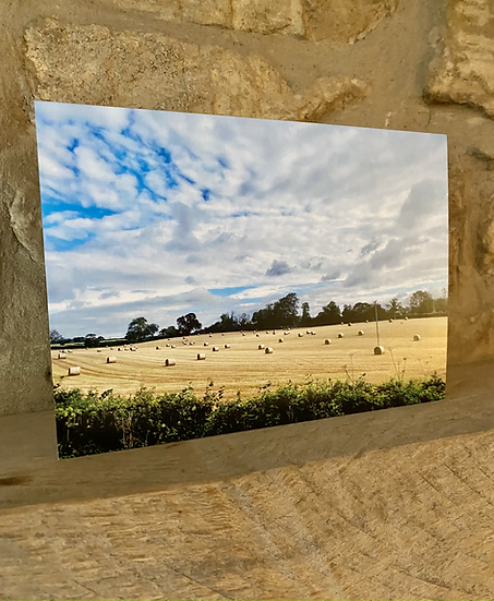 A card showing hay bales in a field in Didmarton