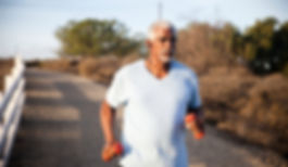 Healthy senior running while carrying weights