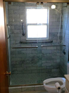 Wider view of the new bathroom with new tile, glass doors and fixtures.