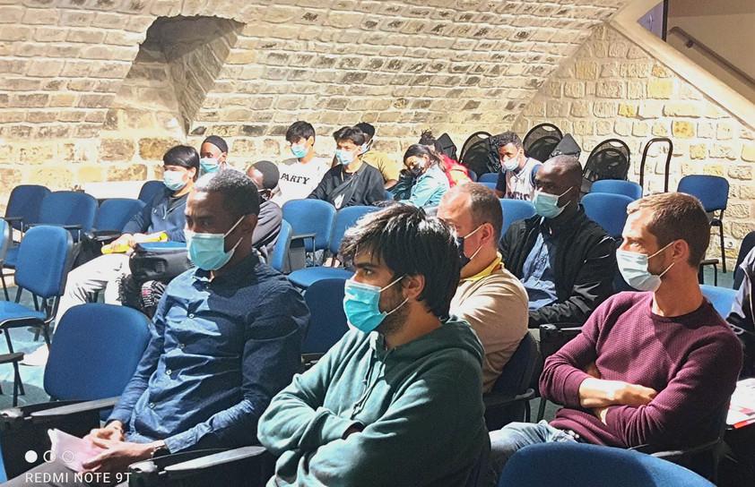 L'équipe AJE-Paris avec en arrière plan, les jeunes du Lycée Erik Satie. présents lors de cette réunion.