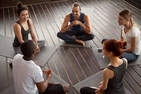 Diverse smiling people sitting on mats i