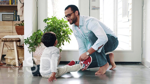 Loving Dad Helps His Preschool Age Son Put On Shoes