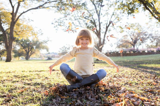 Confident Young Girl Throws Leaves
