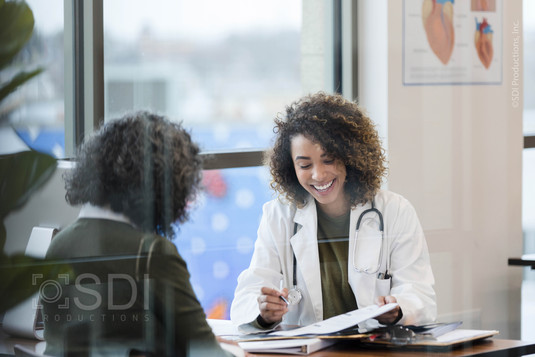 Female Doctor Reviews Diagnosis with Female Patient