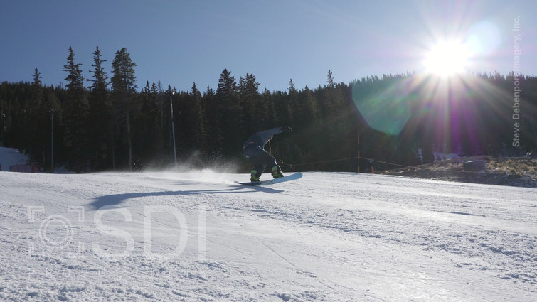 Skillful Snowboarder Jumps As He Nears Bottom of Hill