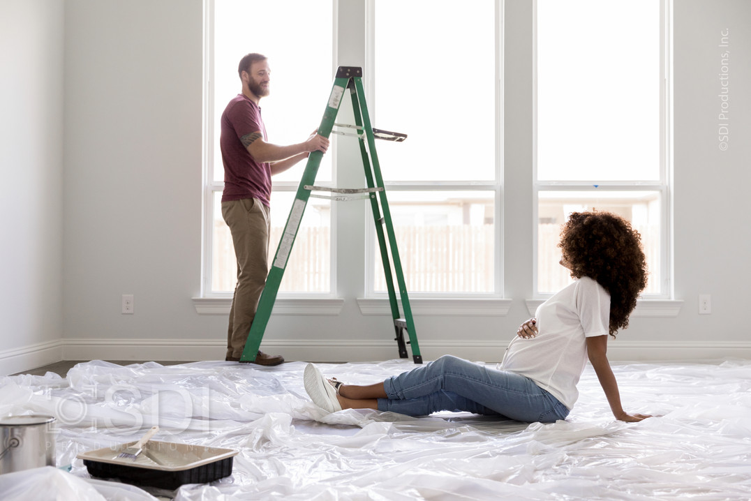 Pregnant Woman Relaxes While Husband Paints Room