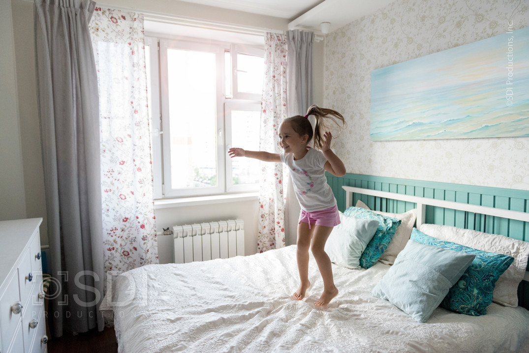 Young Girl Jumps on Bed