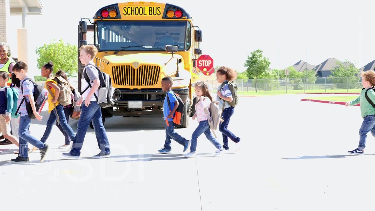 Students Walk Across Crosswalk in Front of School