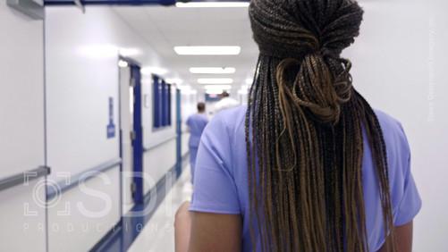 Female Nurse Walking in Busy Hospital Corridor