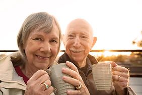Cheerful older couple sitting outdoors w