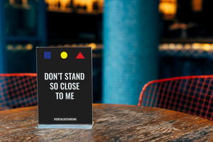 sign on table that says don't stand so close to me.