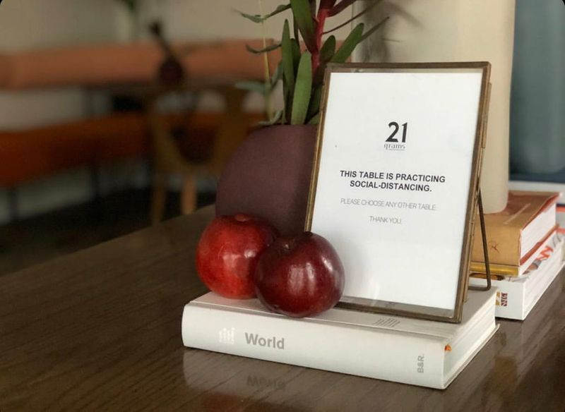 two apples and a picture frame on a table
