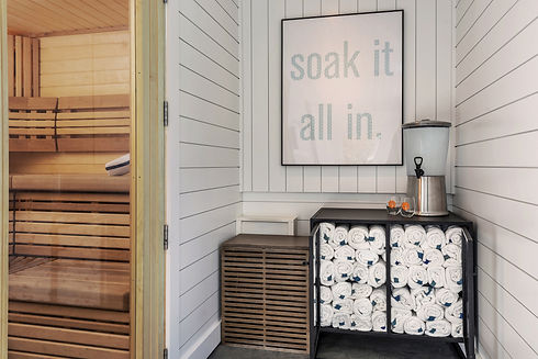 towels staked outside of a sauna with a poster that says soak it all in