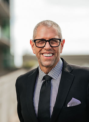picture of a man in a black suit with black glasses smiling