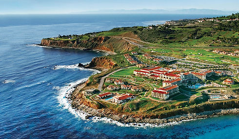 beautiful hotel on the coast with green fields and red roofs