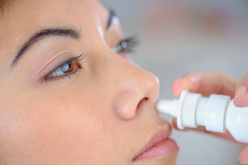Mulher de olhos castanhos aparece lavando nariz com soro fisiológico
