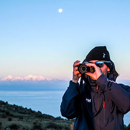 Taking a photo on Sun's Island, Lake Titicaca, Bolivia, sunset mounta ns and moon on the bakground