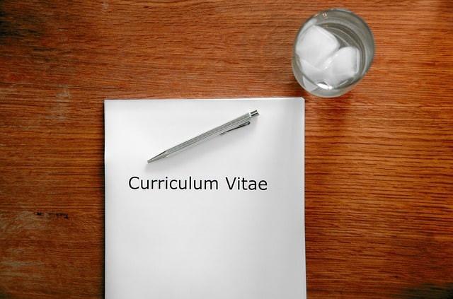 curriculum sobre a mesa e caneta