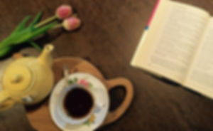 Teapot and a cup of tea on table with flowers and book, literature, pretty