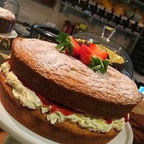 Homemade victoria sponge cake with strawberries, cream and jam