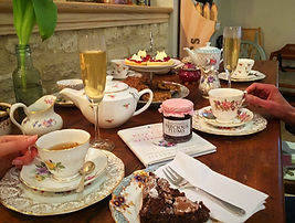 Tea party setup with vintage china, champagne, prosseco, scones and cakes