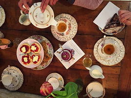 Tea party with vintage china and cups, scones, cakes and prosseco with flowers