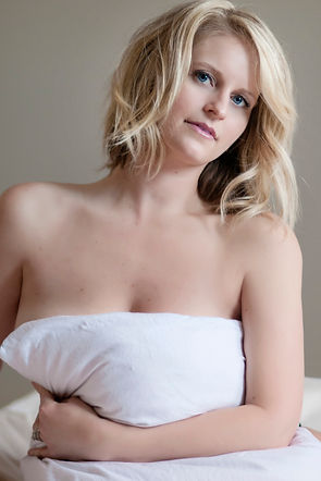 blonde woman looking a camera holding a pillow in front of her