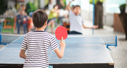 Kid playing table tennis outdoor with family_edited