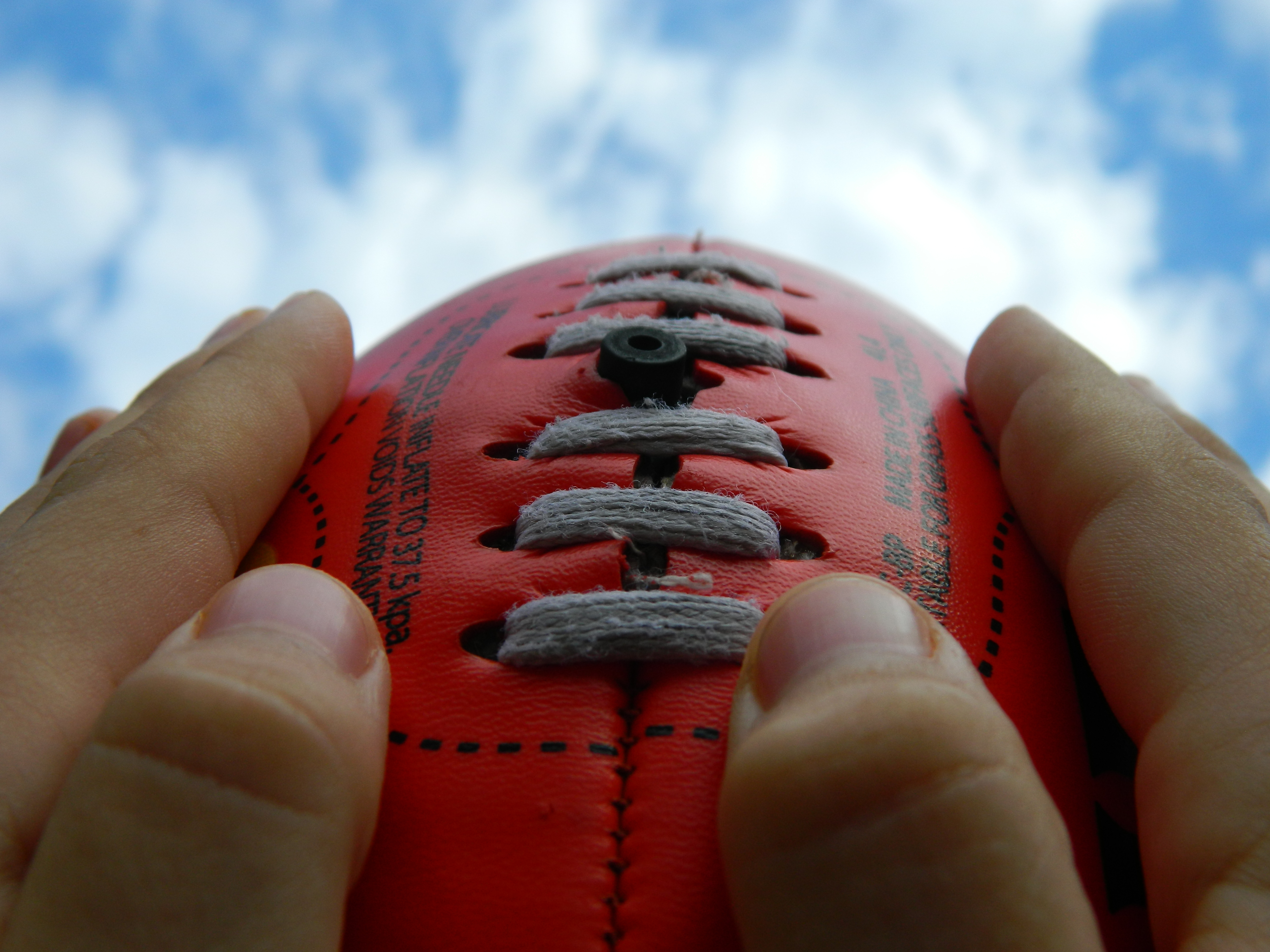 Hands holding football on sky background