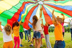 Joyous classmates jumping under colorful