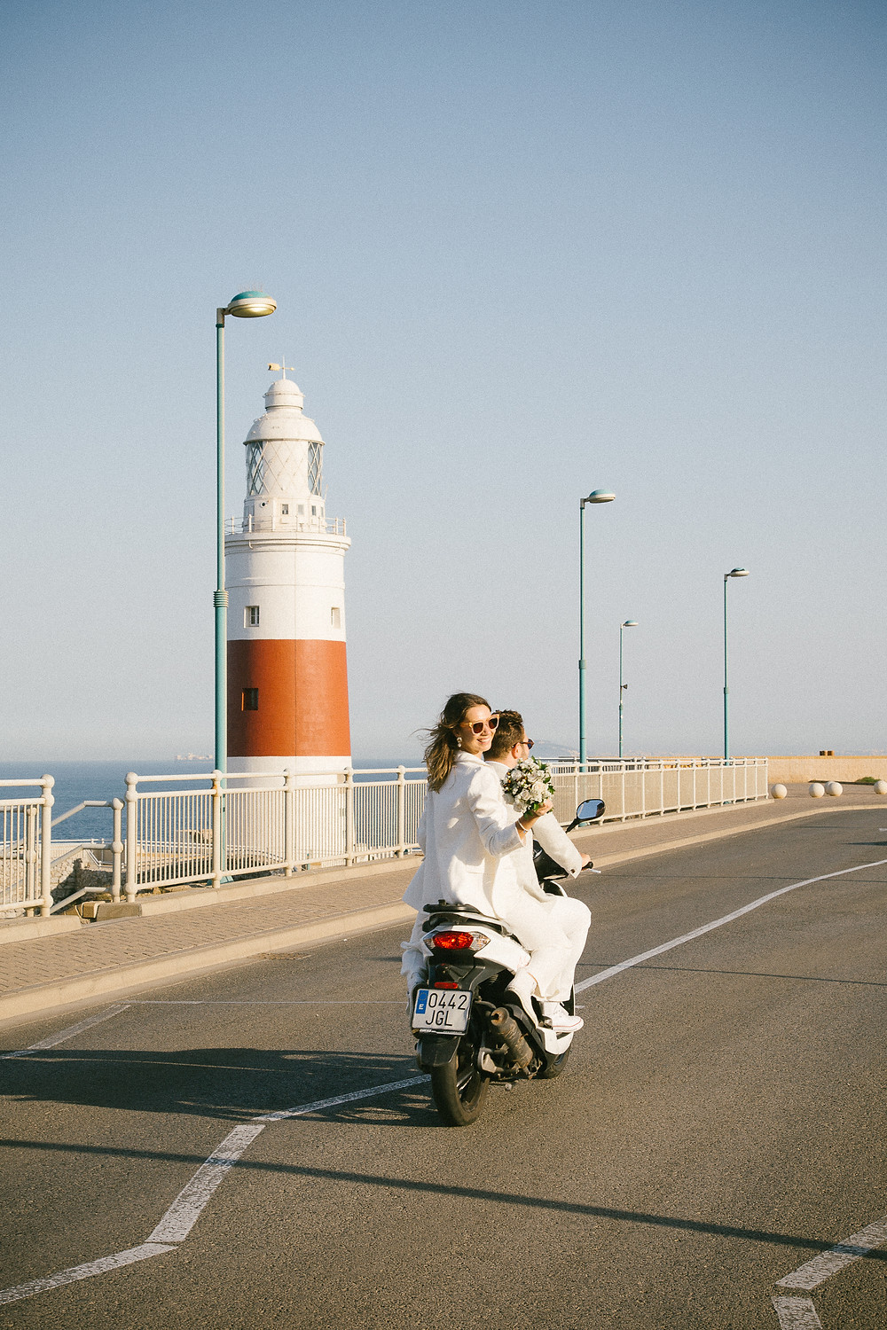 Wedding couple on white moped in Gibraltar