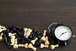 chess-pieces-alarm-clock-wooden-backgrou