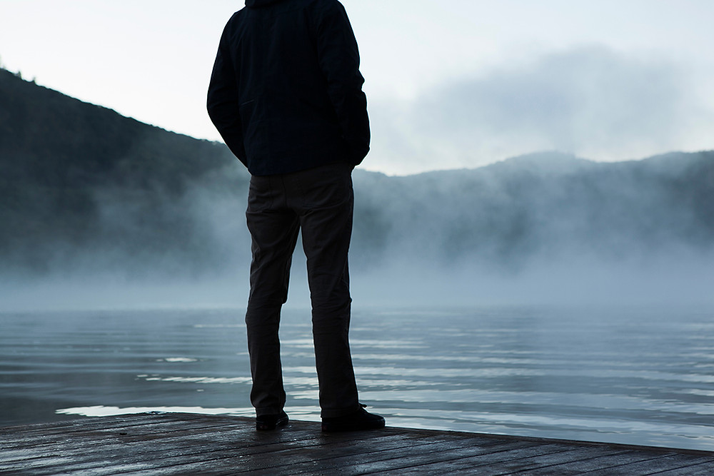 man looking at a lake, misty