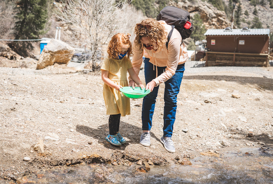 A woman and young girl look into a gold pan near a creek