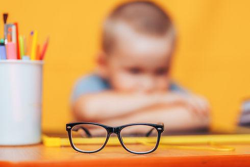 boy sitting ubfocused glasses in focus.