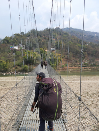 crossing a suspension bridge in Nepal