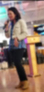 "<img src=""Screenshot_20200213-114028_Video Player.jpg"" alt=""a woman speaking in a microphone wearing dark pants, paisley blouse and a cream denim jacket"">"