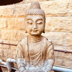 Hand craved stone sitting Buddha