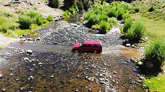 A red truck fords a shallow high-desert river
