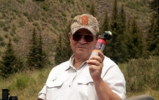 A man in baseball cap and sunglasses displays a can of bear repellant