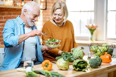Cheerful senior couple eating salad stan