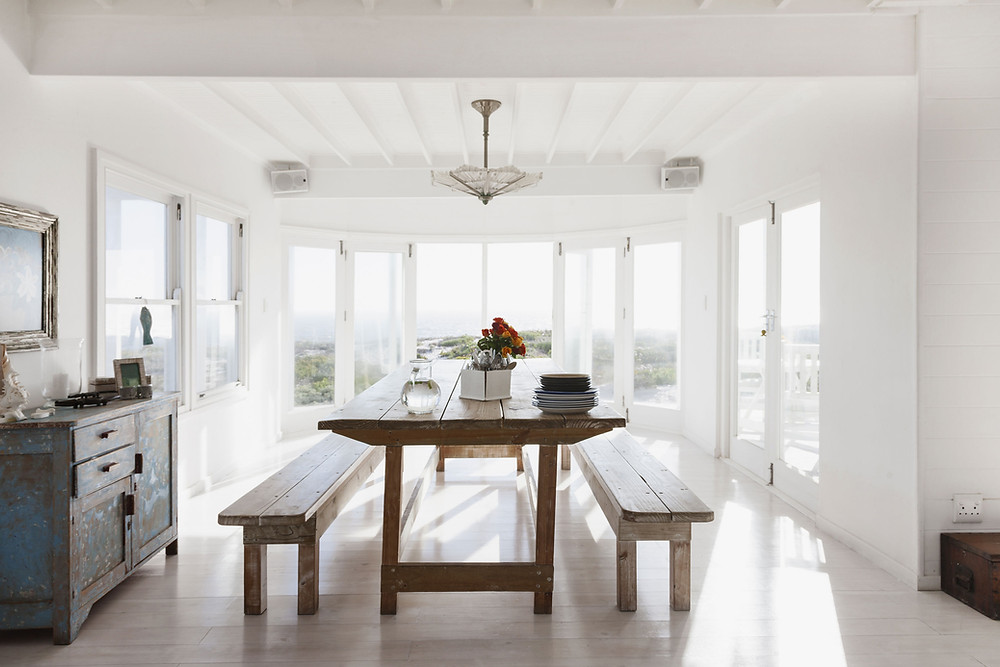 Reclaim Your Dining Room Table - Photo of rustic dining room table in front of balcony doors and windows