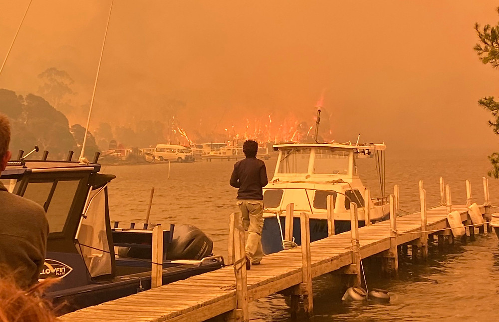 People watch on from Mallacoota's pier as fire surrounds the coastal destination.  (Photo by Billilee Williams. Used with permission.)